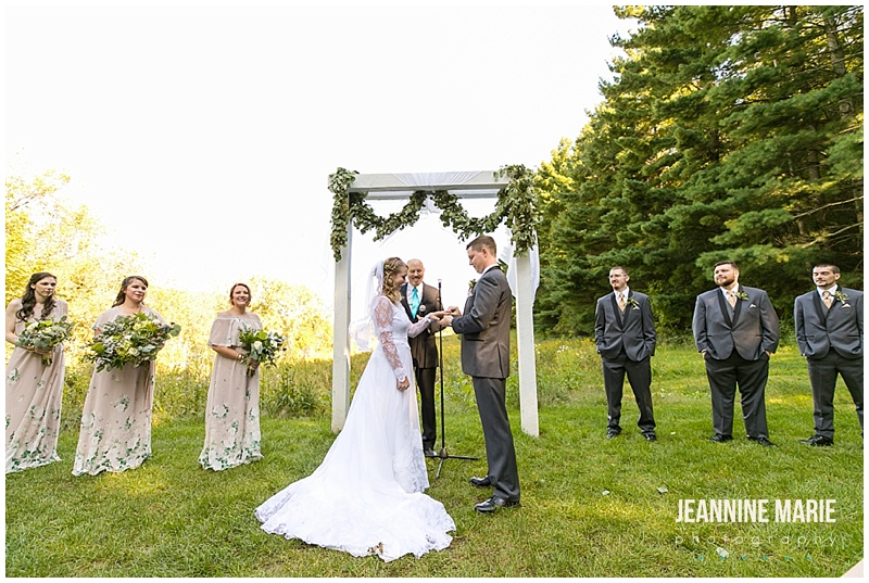 ring exchange, outdoor wedding, floral arch, wedding party, bride, groom, rings, wedding rings, The Round Barn, Jeannine Marie Photography, Minnesota wedding photographer, Saint Paul wedding photographer, barn wedding, farm wedding, rustic wedding, Minnesota barn wedding, Minnesota farm wedding, vintage wedding gown, vintage wedding, Heather Rosales, Artemisia Studios, A'Britin Catering, Valley Pastries, Midwest Sound, Roadkill, Liana Harding, Katie Brown Studios, JenMar Creations, DSW, ShowMeYourMumu, Savvi Formalwear, Minnesota Coaches, wedding inspiration, Minnesota wedding, Round Barn Farm wedding photographer, outdoor wedding, field wedding, September wedding, Minnesota Bride, Midwest Bride